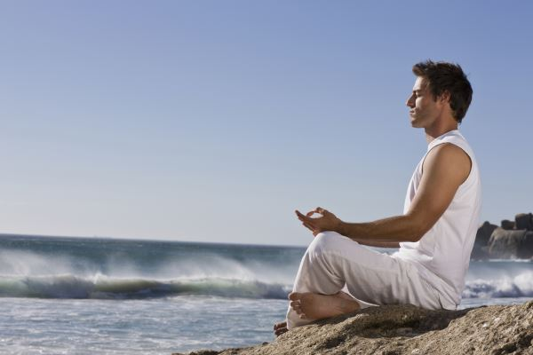 Handsome young man meditating on rock by sea