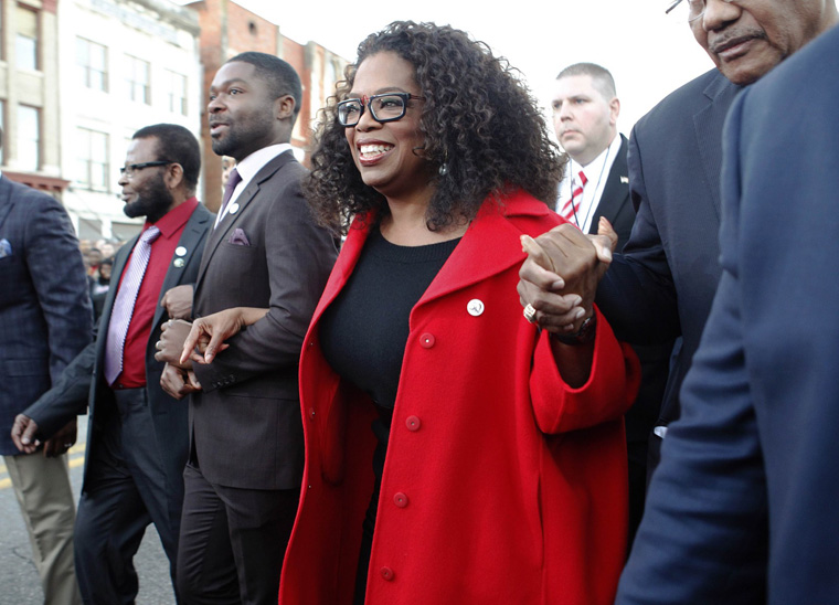 """Oprah Winfrey, producer and cast member of the movie """"Selma"""", locks arms with actor David Oyelowo as they participate in a march in Selma, Alabama"""